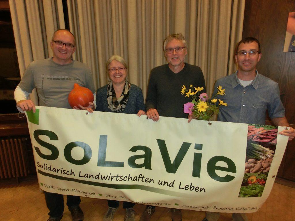 Foto: vier Personen (Vorstand der SoLaVie, 3 Männer, eine Frau)) in einer Reihe mit dem Banner der SoLaVie in den Händen, sowie ein Blumenstrauß, ein Kürbis